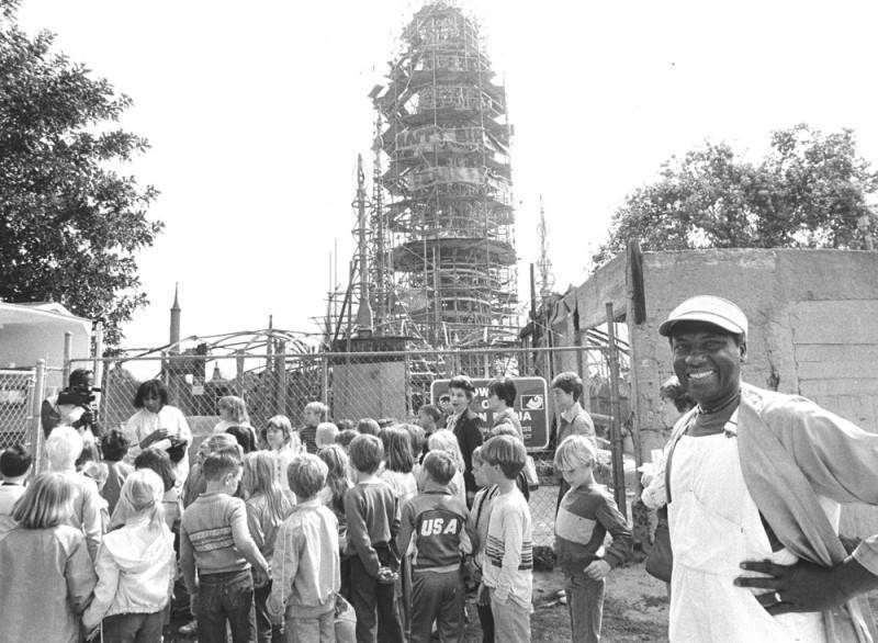 John Outterbridge (right), director of Watts Towers Art Center, seen with a group of students, from the El Segundo Center St. Elementary School, who are touring the Watts Towers. March 22, 1985 | Herald Examiner Collection, Los Angeles Public Library