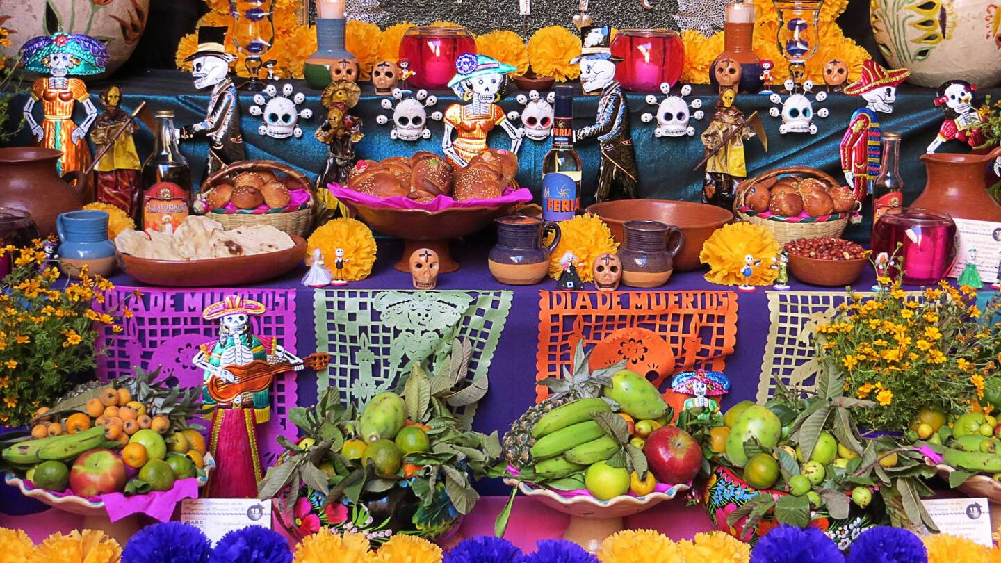 A Day of the Dead altar is covered in flowers, bread, decorative skulls and intricately cut brightly colored paper.