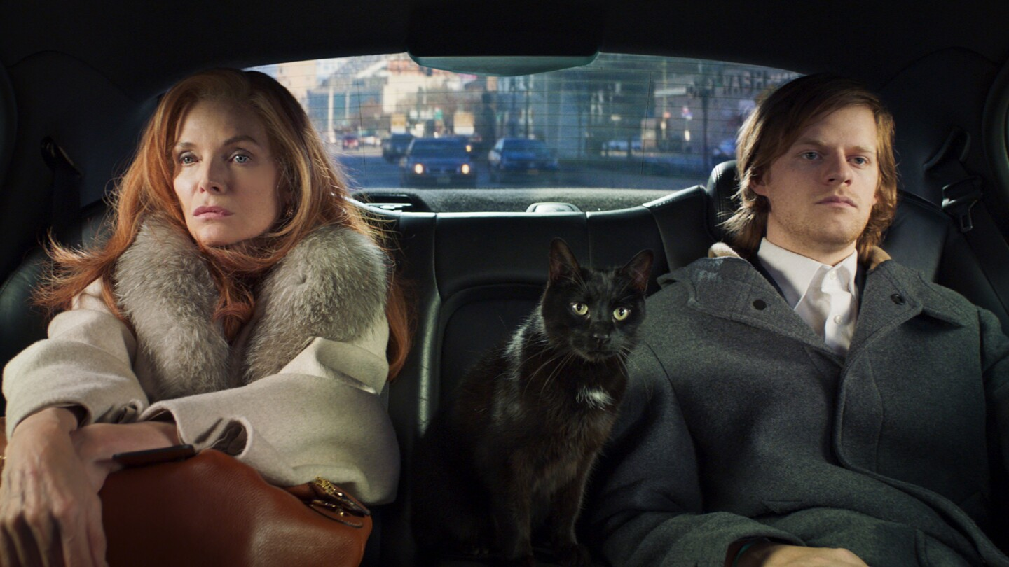 A woman and her adult son sits in the back of a car with a black cat between them.