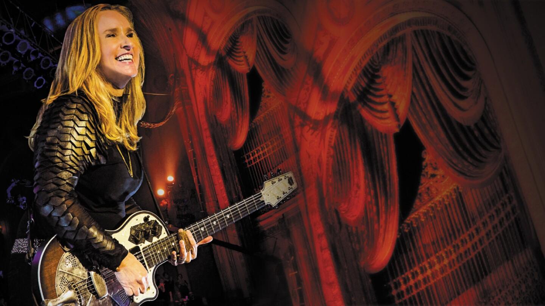 Melissa Etheridge performing on her guitar.