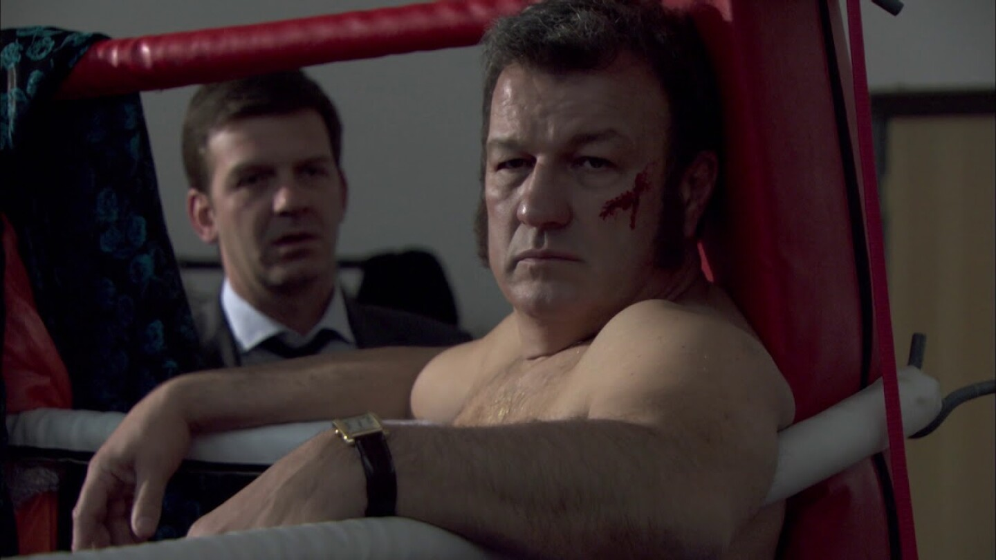 Scene from Midsomer Murders: shirtless man with a cut on the cheekbone wearing a watch sitting in corner of boxing ring