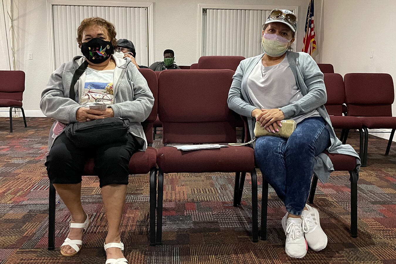 Two woman sit in waiting room chairs with an empty chair between the two of them. THey're both wearing masks and have their hands folded on their lap.