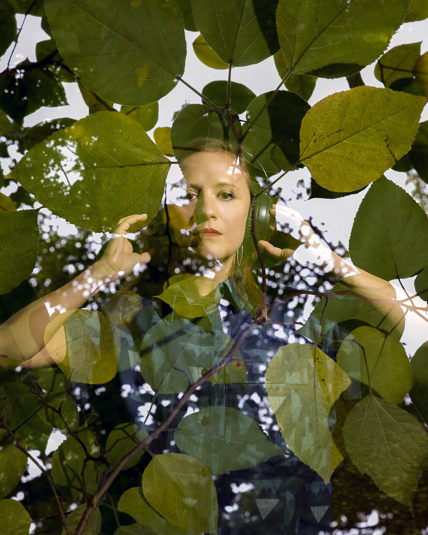 A woman wearing headphones overlaid with leaves