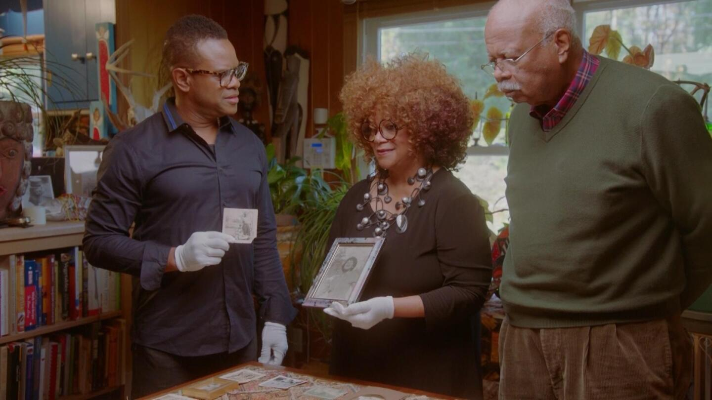 """Host Thomas Allen Harris listens to a woman speaking about her family photo. 