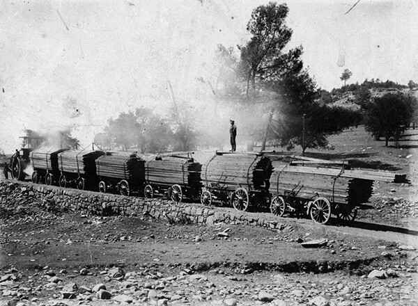 Train of cars carrying lumber being pulled by a logging tractor in Central California. Lumber was also extracted from the San Gabriels. | Courtesy of the Los Angeles Public Library