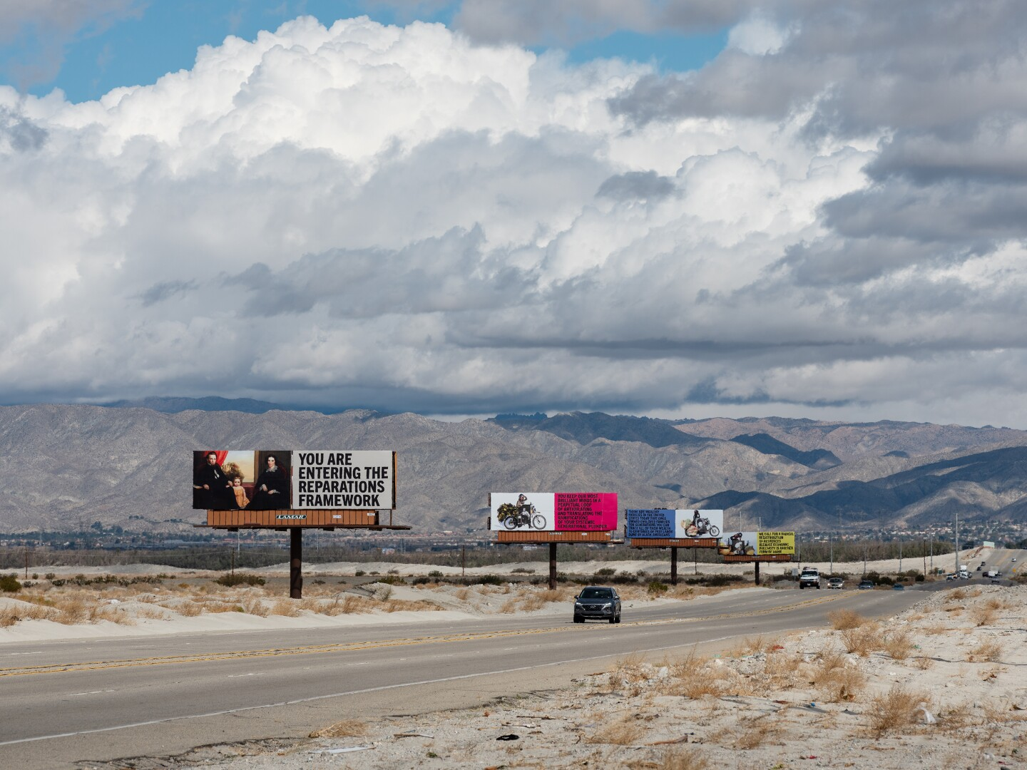 """Xaviera Simmons' billboard art installation, """"Because You Know Ultimately We Will Band a Militia,"""" for Desert X 2021 stands along the Gene Autry Trail. Four billboards stand in a line. The one closest to the foreground reads, """"You are entering the reparations framework."""" A car drives down the road that runs along the billboards."""