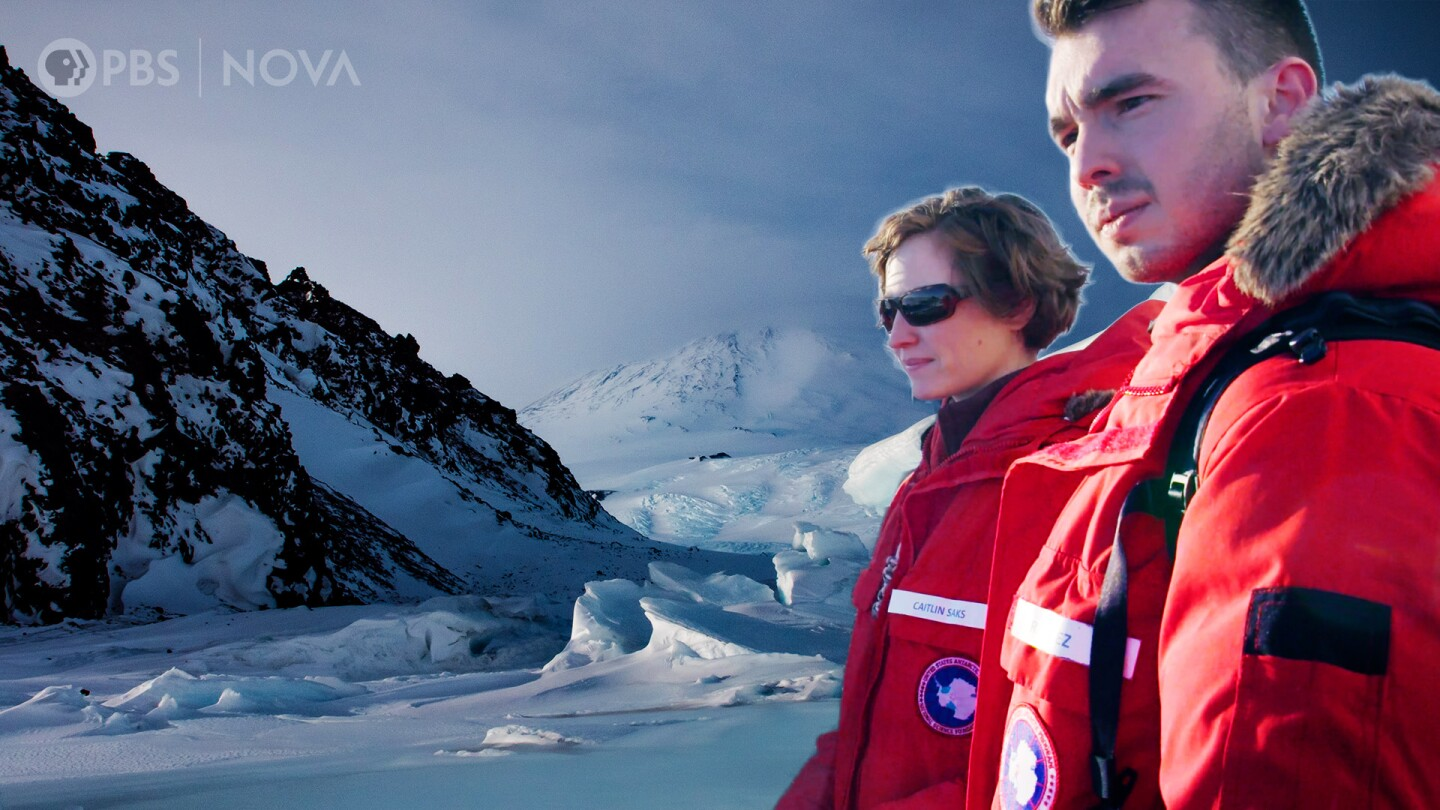 "A man and a woman in thick red winter coats in a thumbnail image for ""Antarctica: Journey to the Bottom of the Earth."""