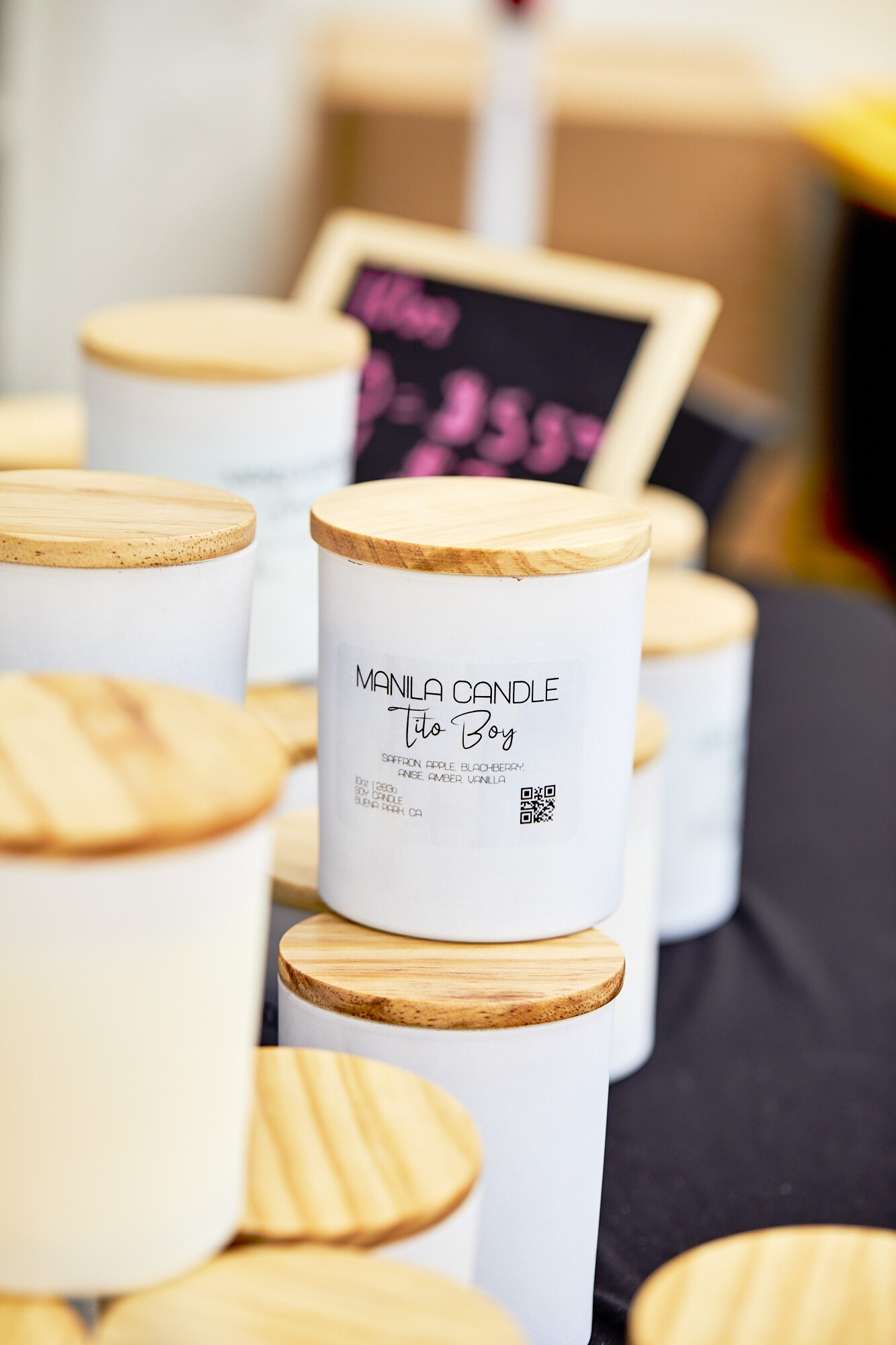 """The Tito Boy candle sits at the Manila Candle booth at the FilLed Market in Downtown L.A.  The candle body is white and reads, """"Manila Candle, Tito Boy"""" in black print. The candle lid is a light-colored wood."""