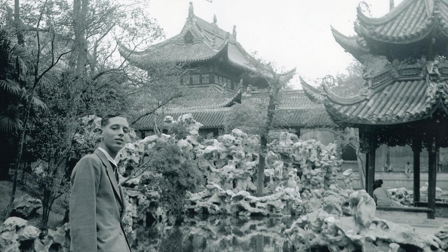 A man looks into the camera as he stands in a Chinese garden.