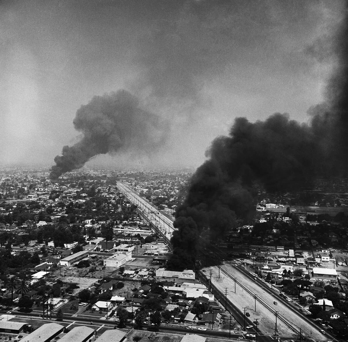 Black smoke darkens the sky over Southeast Los Angeles, during the fourth day of the Watts Uprising | Getty Images