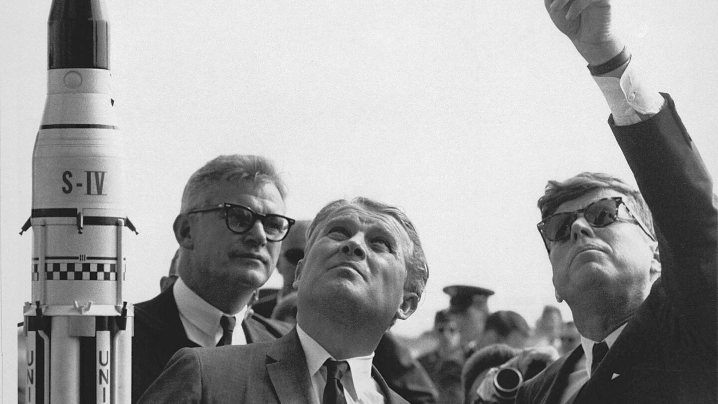 "Dr. Wernher von Braun explains the Saturn Launch System to President John F. Kennedy. NASA Deputy Administrator Robert Seamans is to the left of von Braun. | ""Blue Sky Metropolis: A Space Odyssey"""