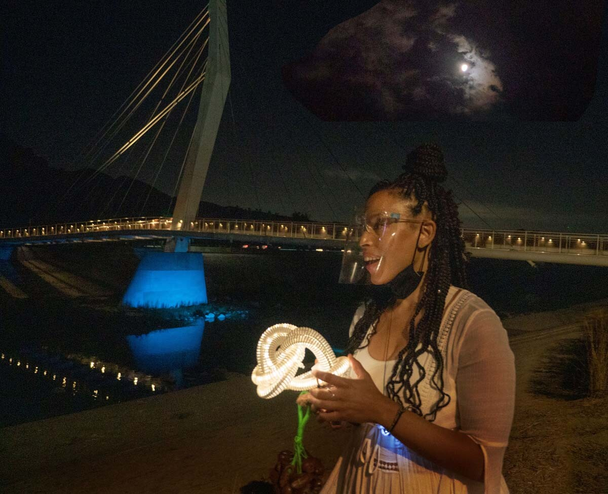 "A perfomer wearing a face mask by the North Atwater Multi-modal Bridge. The performance is part of at ""Firefly Nights,"" an in-person COVID-safe experience that falls within the ""Rio Reveals"" series."