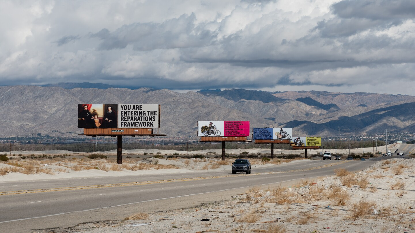 "Xaviera Simmons' billboard art installation, ""Because You Know Ultimately We Will Band a Militia,"" for Desert X 2021 stands along the Gene Autry Trail. Four billboards stand in a line. The one closest to the foreground reads, ""You are entering the reparations framework."" A car drives down the road that runs along the billboards."