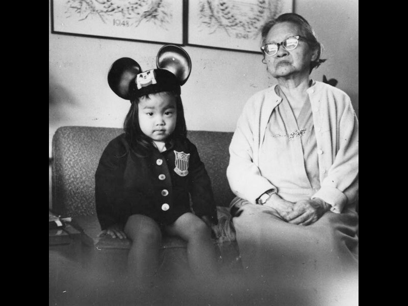 Black and white photo of a Korean American child in mouse ears sitting on a couch with her grandmother
