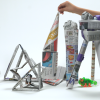 Several shapes and structures made out of newspaper are peppered with small toys.