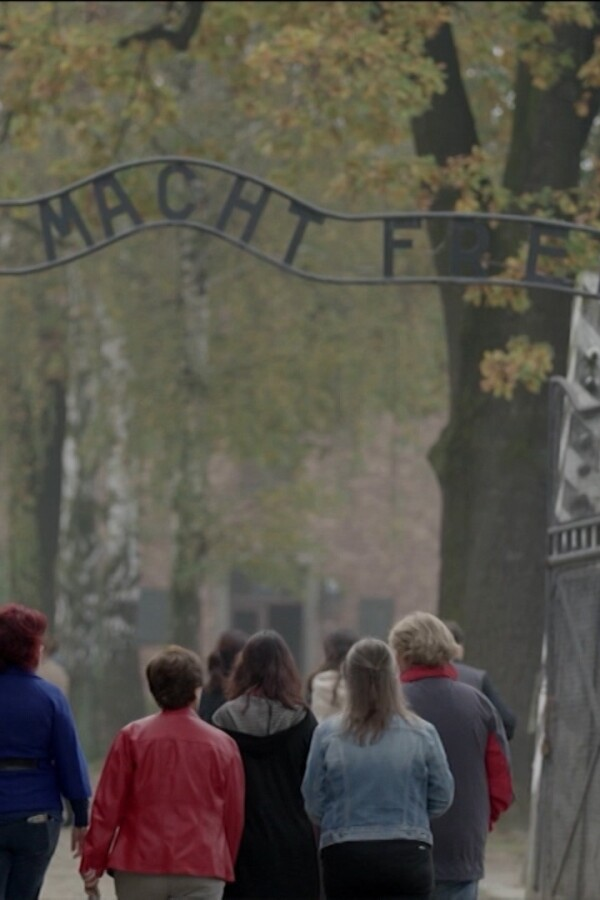 """A group of people walk under a sign that says """"Arbeit Macht Frei,"""" or """"work sets you free."""" 