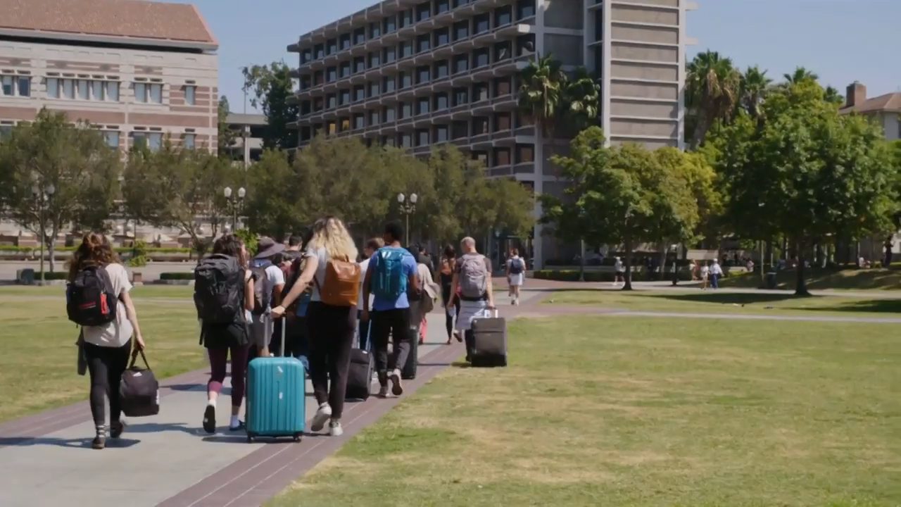 A group of college students with their suitcases make their way across the USC campus.