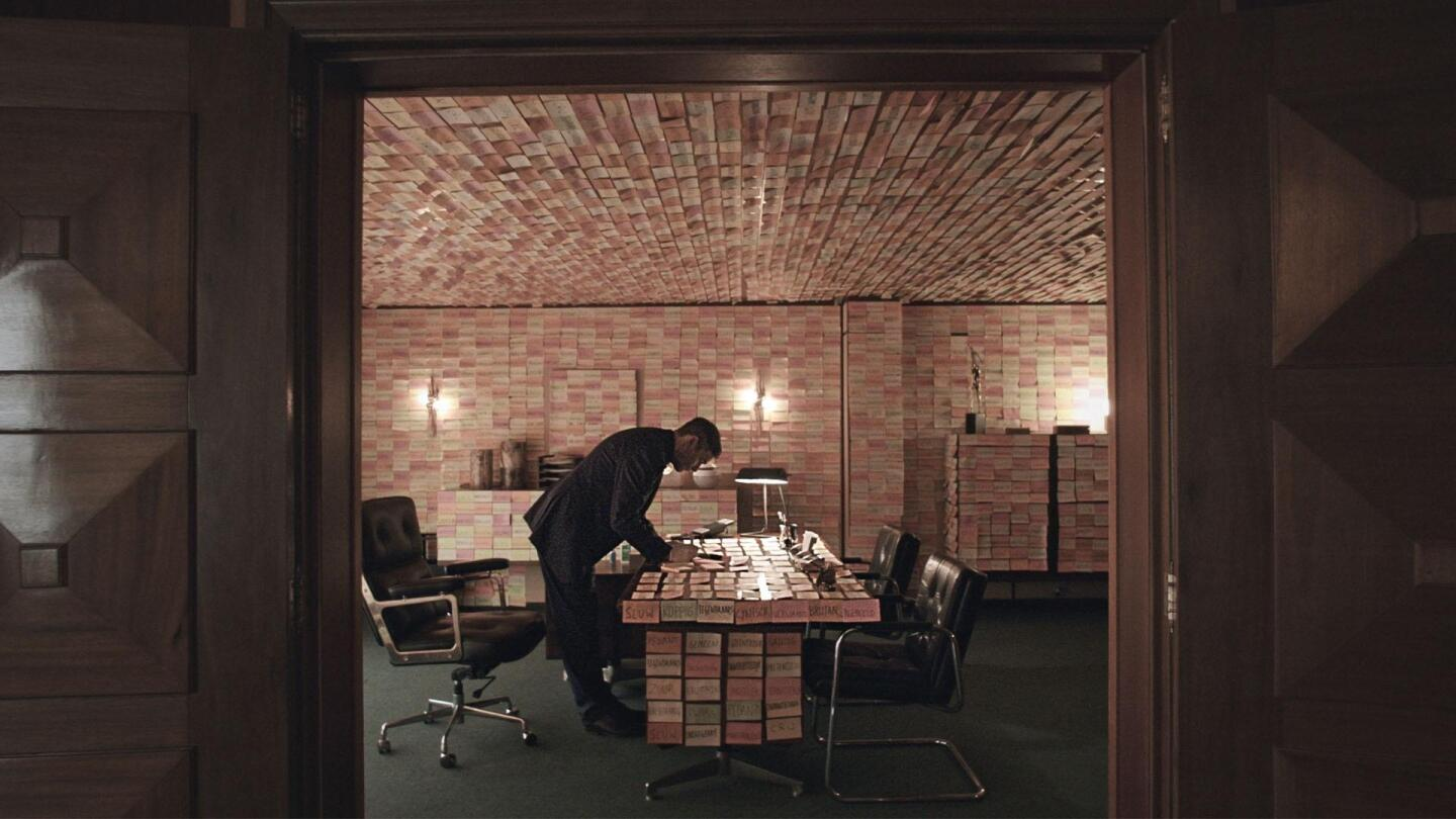 "Professor T (Koen De Bouw) writes on a sticky note on a desk in a room plastered with hundreds of other sticky notes. | ""Professor T Season 2: Attachment Issues"""