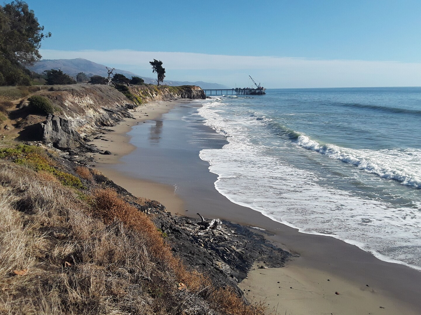 A wave pushes in on the shore of Carpinteria State Beach as a small hill of black tar builds right at the start of the beach.