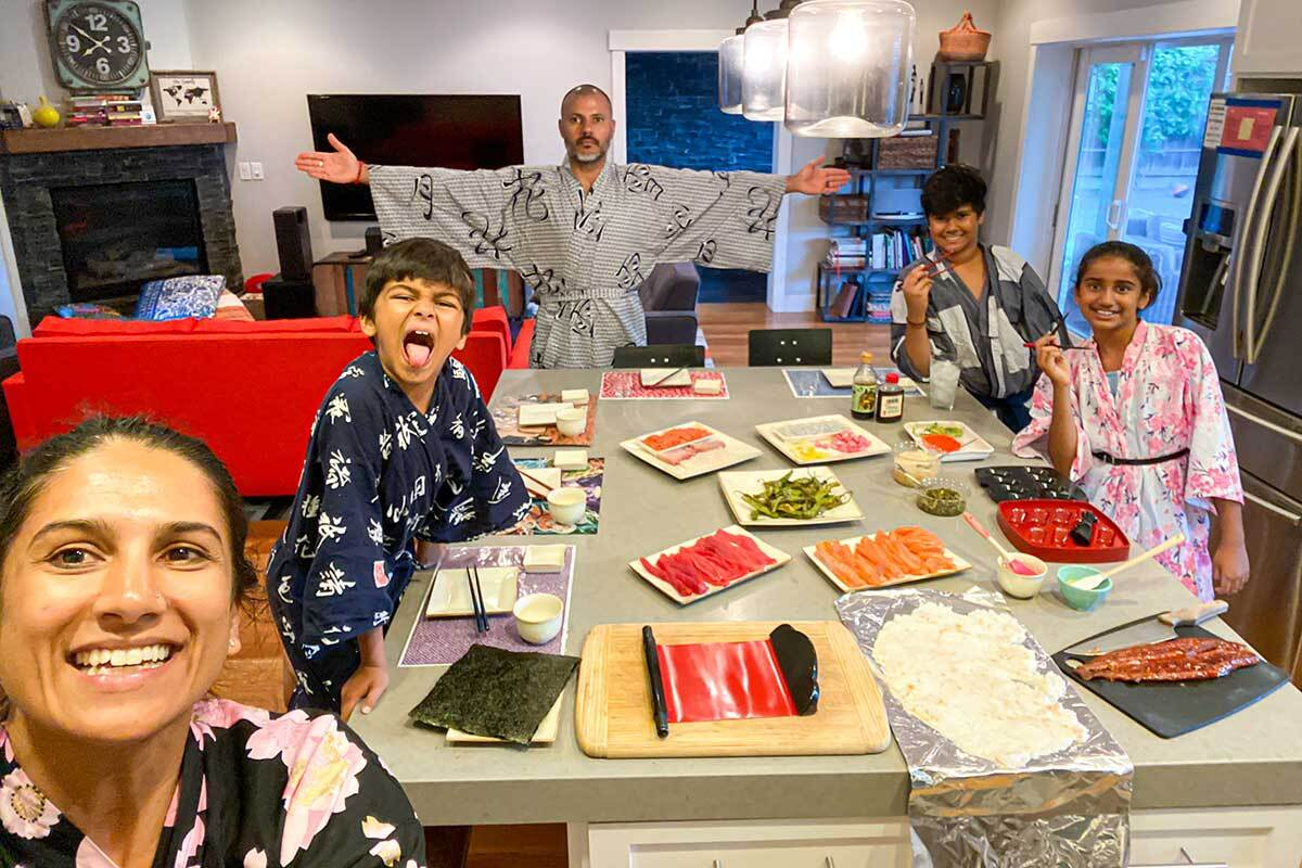 A family poses around a table laid out with ingredients to make sushi.