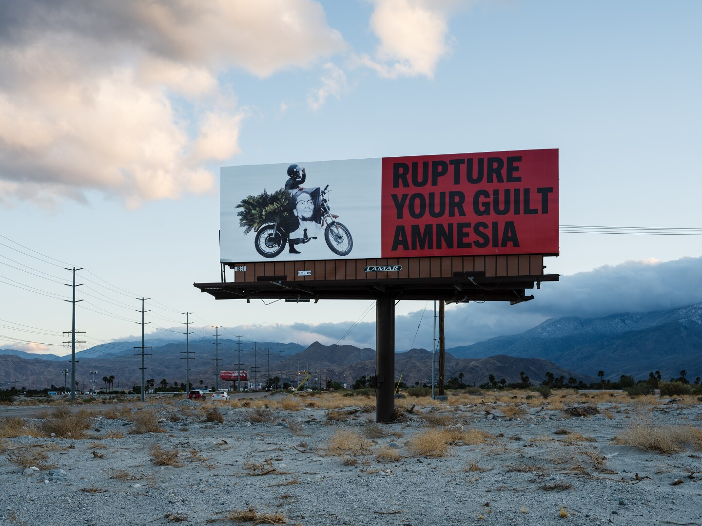 """A billboard part of Simmons' art installation, """"Because You Know Ultimately We Will Band a Militia,"""" reads, """"Rupture your guilt amnesia."""""""