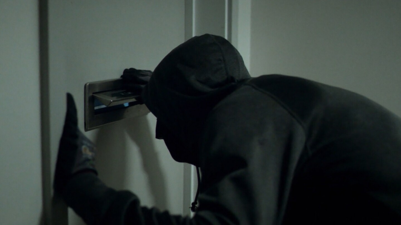 "A man wearing dark clothes looks through a door's mail slot. | Still from ""Follow the Money"" Season 2, Episode 5"