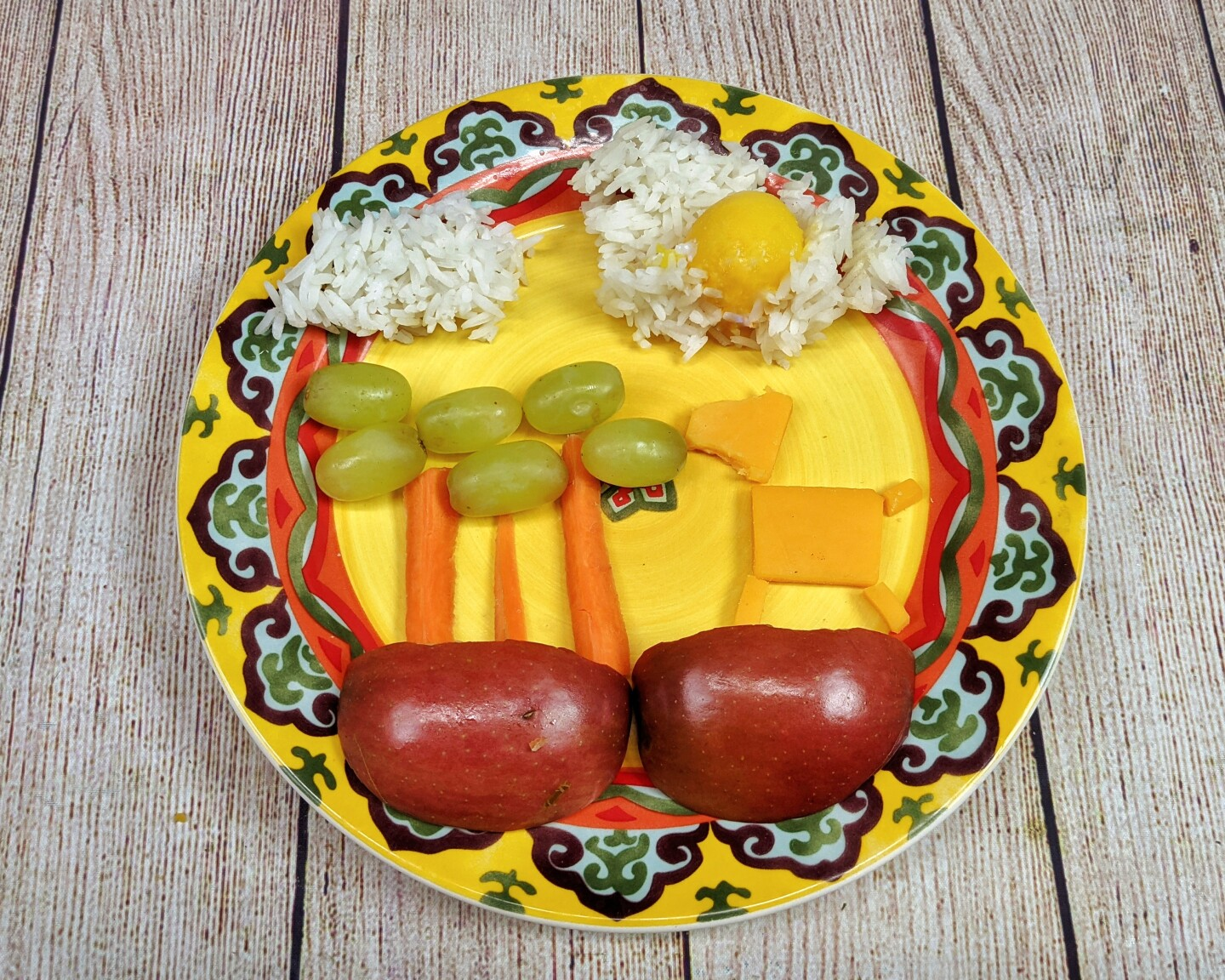 cheese, apples, carrot slices and grapes are arranged in the shape of a cheese farm animal eating grapes from carrot stick trees.