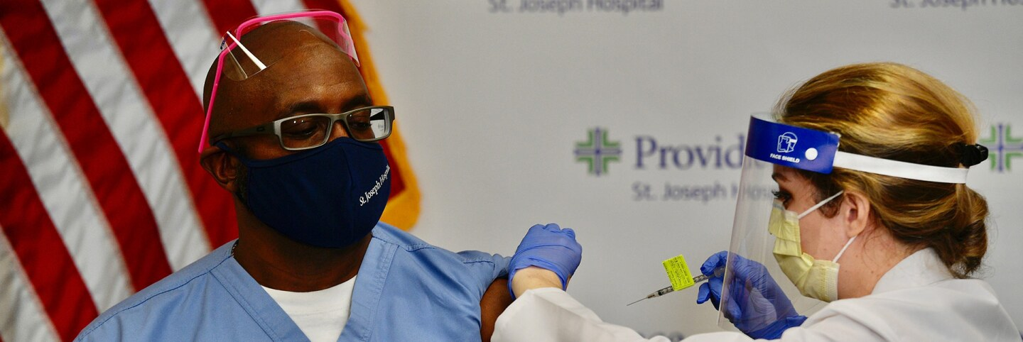 Nurse Michael Lowman gets the first dose of the Pfizer BioNTech COVID-19 vaccine from nurse practitioner Christie Aiello at Providence St. Joseph Hospital in Orange, CA, on Dec. 16, 2020. | Jeff Gritchen/MediaNews Group/Orange County Register via Getty