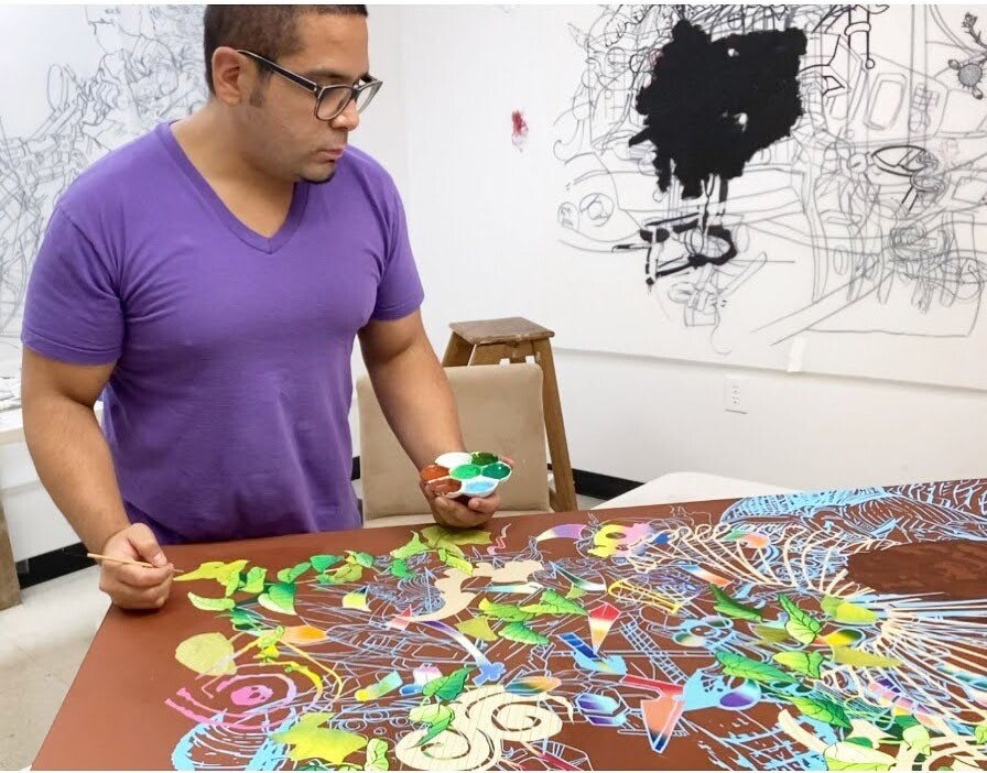 Artist David Rios stands over one his works in his art studio.