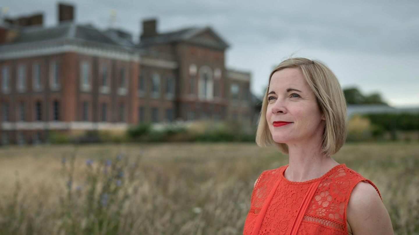 Lucy Worsley looks on in a field outside a grand building.