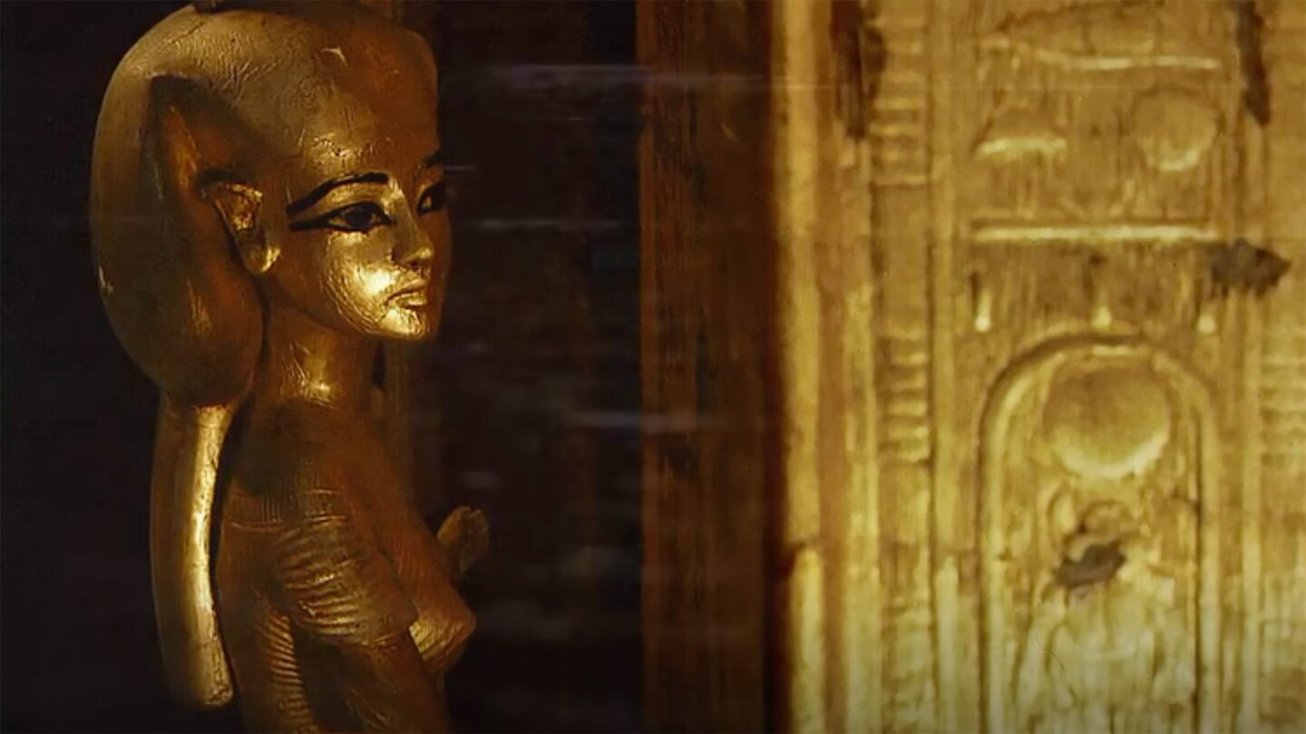 An Egyptian gold statuette of a woman with a headdress