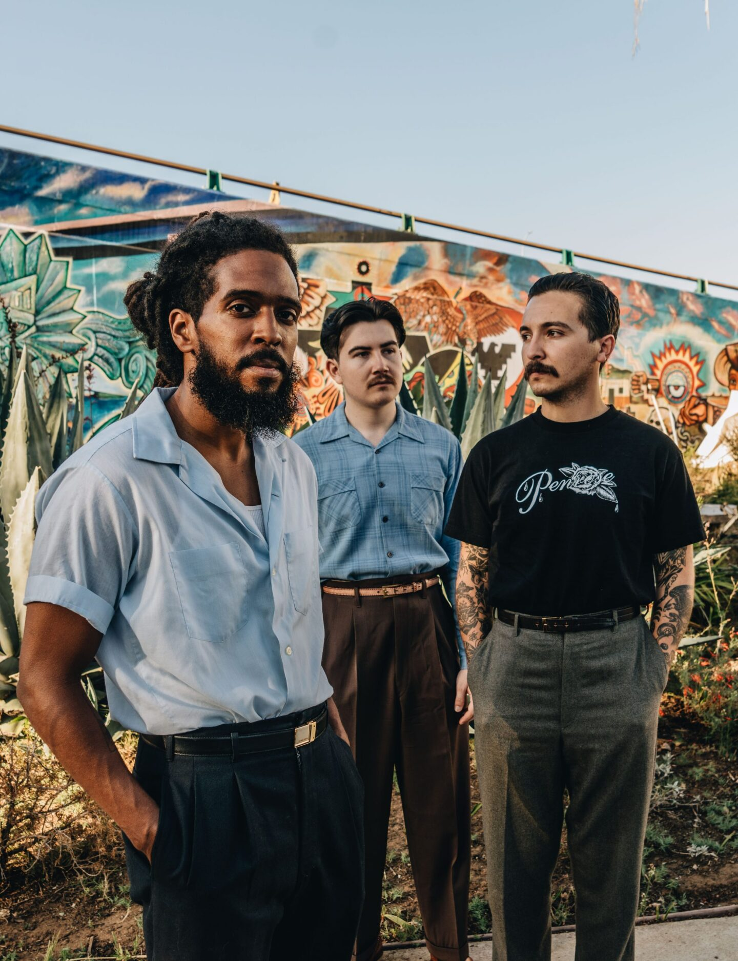 The members of Thee Sacred Soul, Sal Samano, Alex Garcia and Josh Lane, stand together in front of a mural.