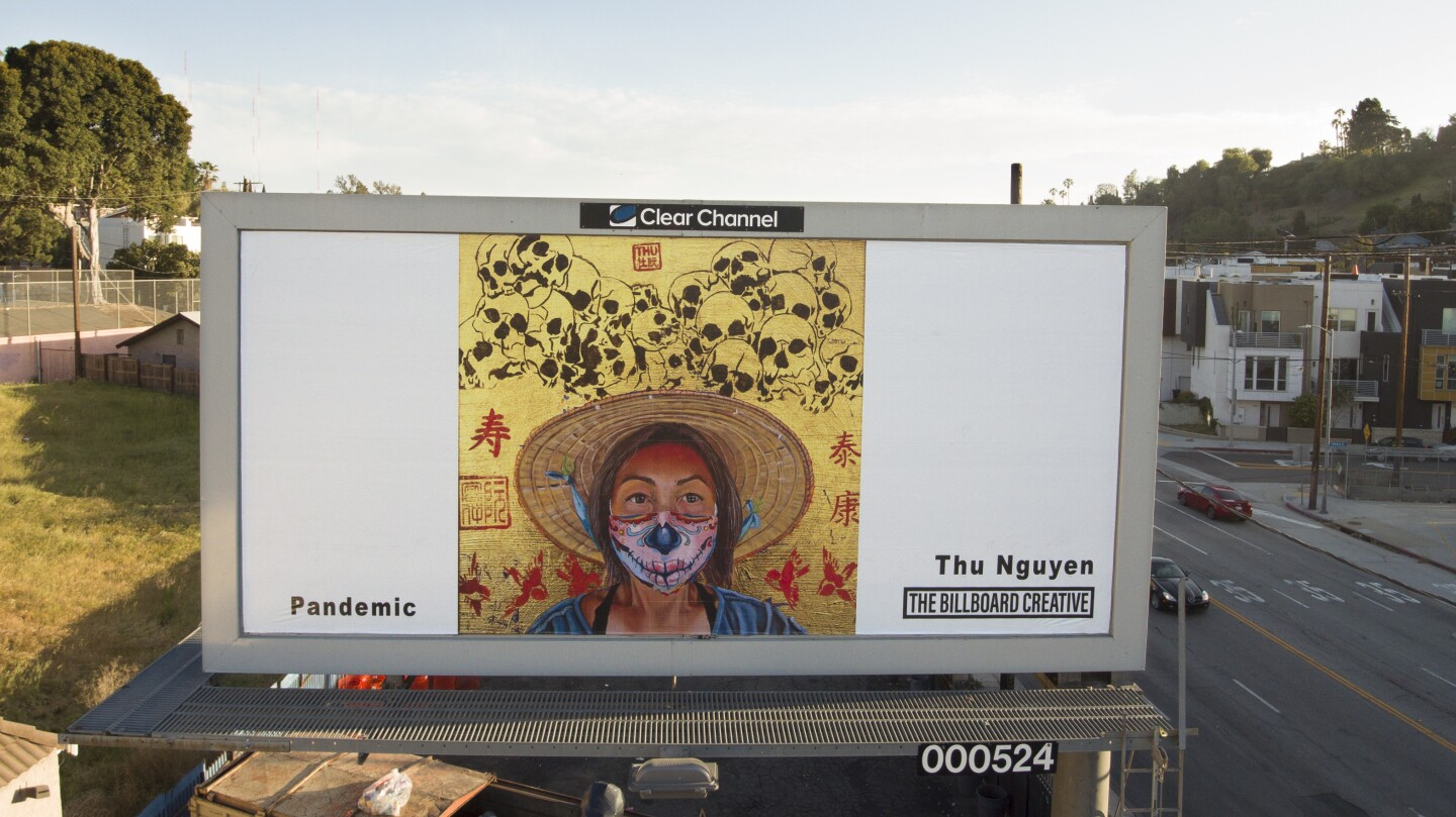 A billboard shows a portrait of a woman wearing a woven hat and a face mask. Behind her is a gold background and a pile of skulls drawn on.