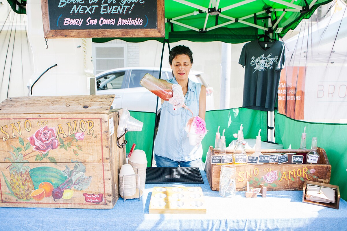 Sno con Amor's owner Lauda Flores making a snow cone in her stall at Hollywood Farmers' Market. | Jenny Kim