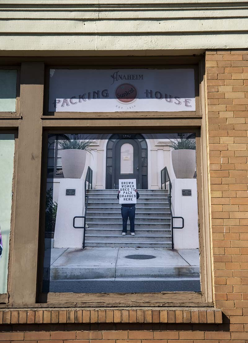 """William Camargo holds up a sign that says, """"On this side of the wall is a predominantly Brown working class neighborhood"""" as part of his exhibition, """"Origins and Displacements, Vols. 1 & 2"""" at MUZEO 