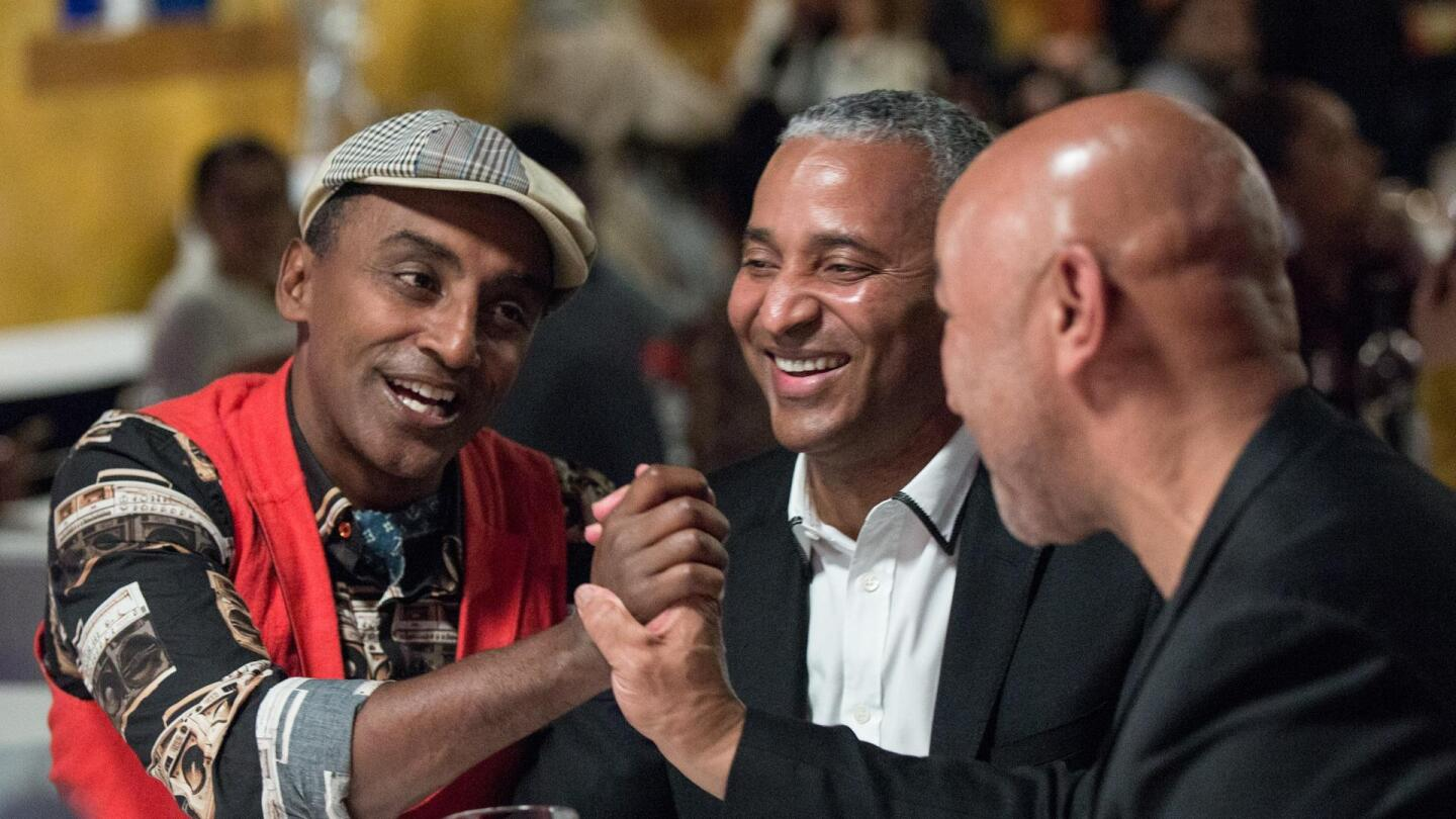 "Chef Marcus Samuelsson grabs the hand of a bald man in ""No Passport Required: Boston."""
