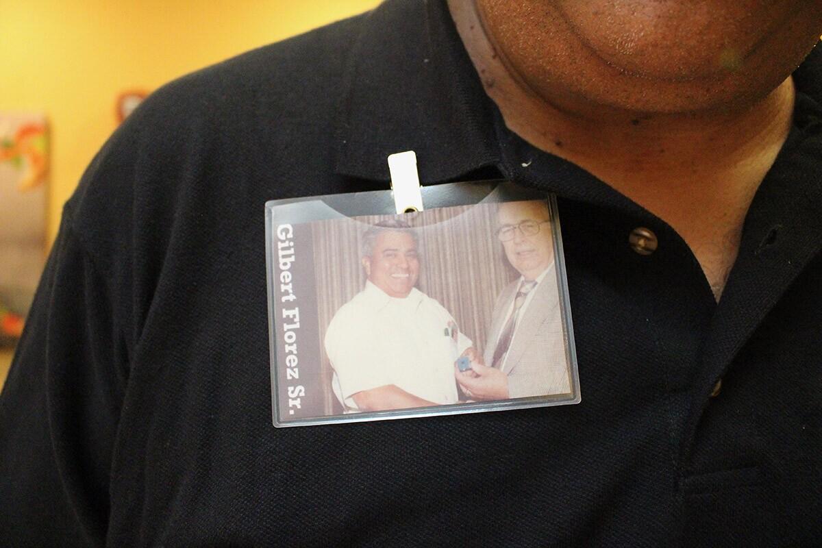 Gilbert BevenFlorez Jr. wears a badge with a photo of his father, Gilbert Florez Sr. | Jean Trinh