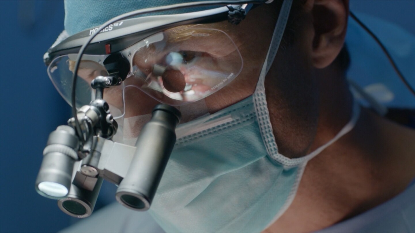 """A surgeon wearing surgical loupes and a face mask. 