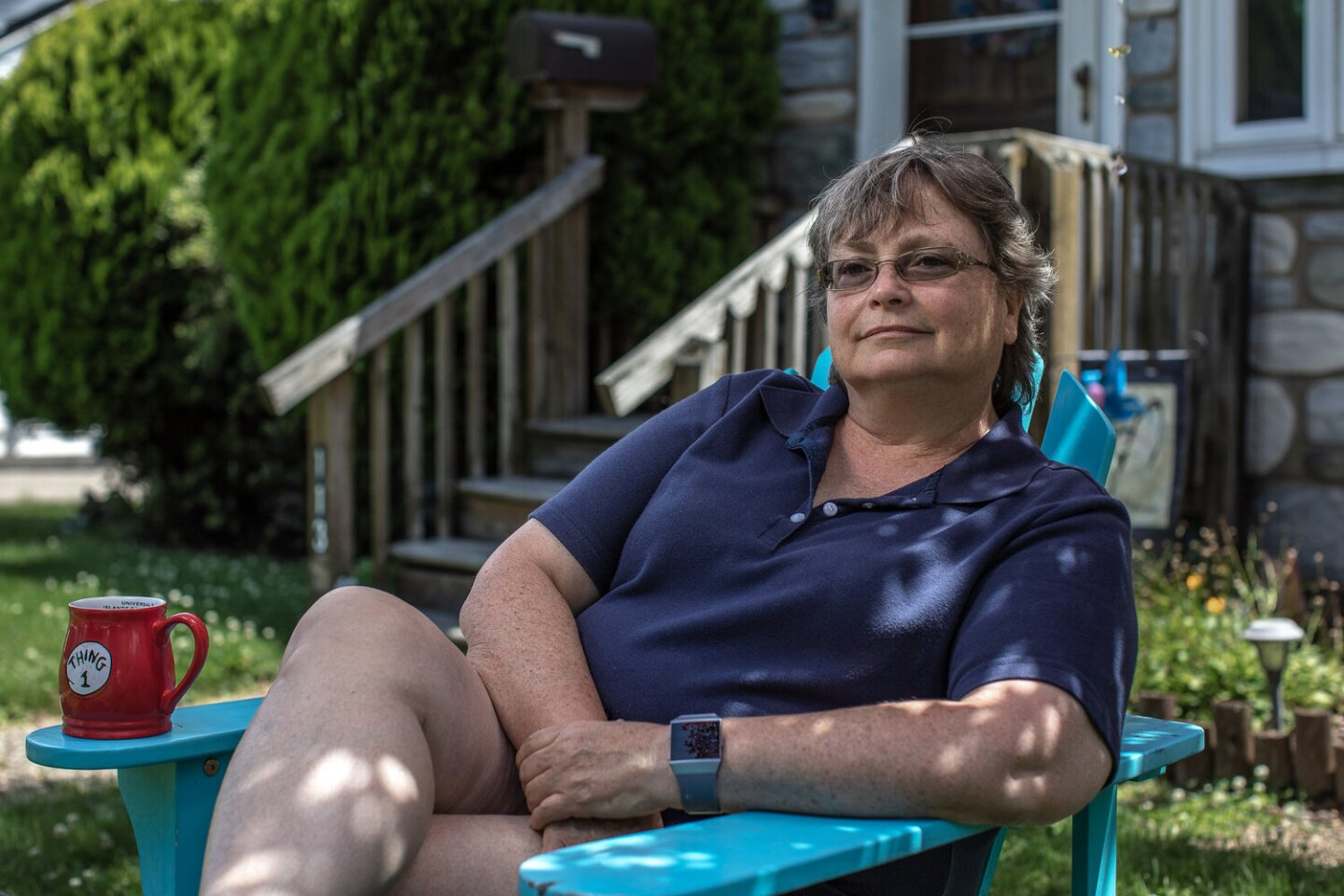 Susan sits on a bright blue wooden lawn chair. She's sitting leaned back, with her legs folded and her arms crossed. Patches of sunlight light different parts of her body as she smiles with a gaze slightly off from the camera.