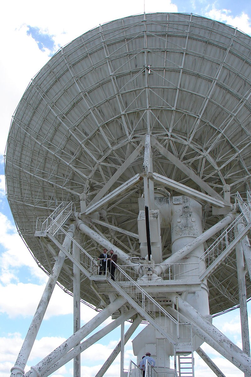 A giant white radio telescope with some people on a platform near its top.
