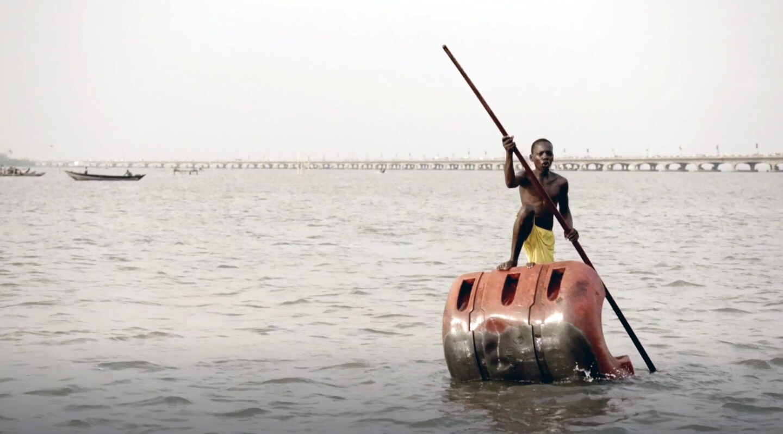 A boy rows in a lake in modern-day Benin