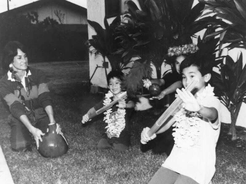 Three children sitting on a lawn perform traditional Hawaiian music using pu'ili (the long bamboo instruments), 'uliuli (the feather gourd rattles), and the ipu (the large gourd) in this black and white photo, circa 1985