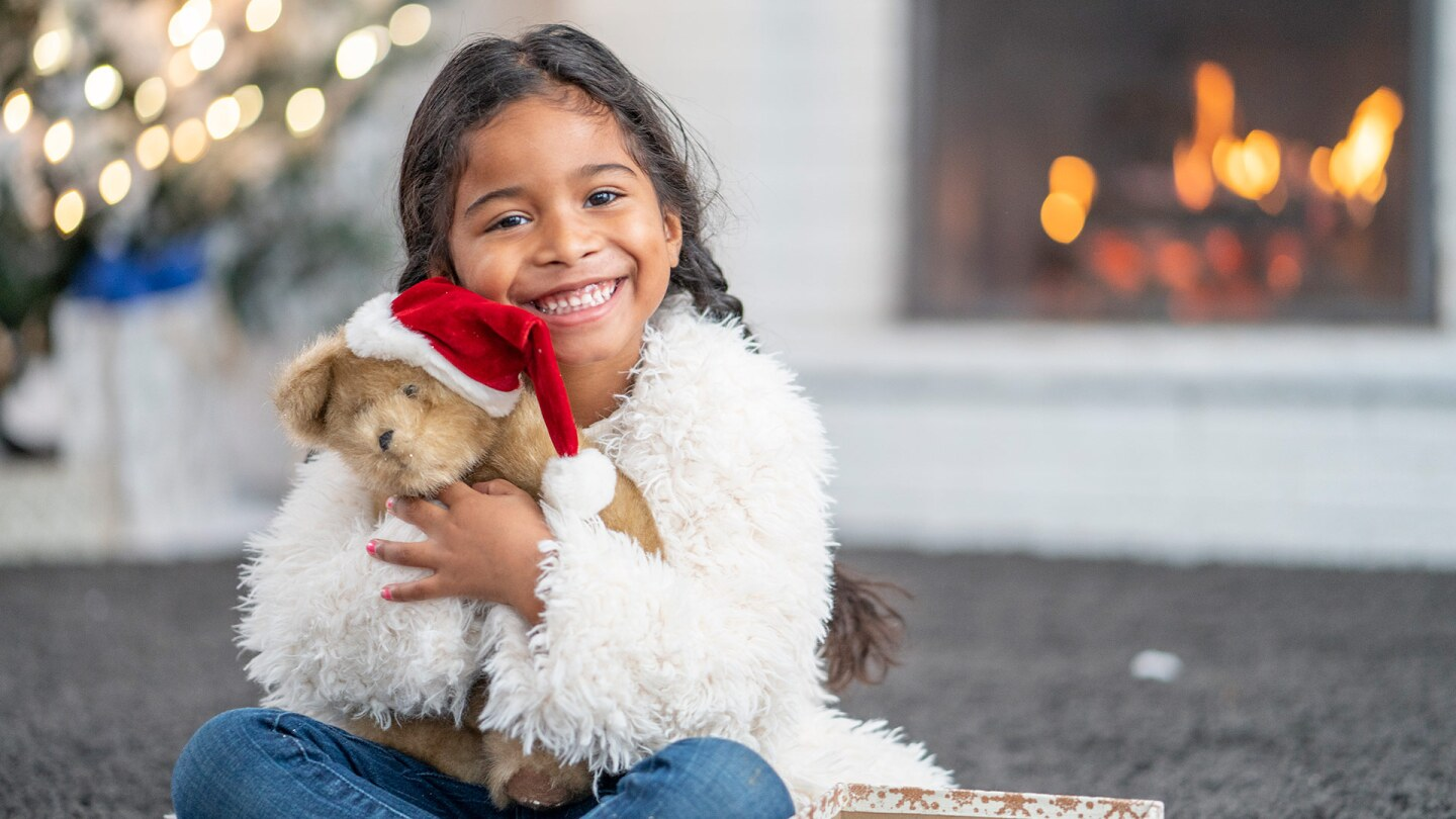 A small child sits in front of a fireplace and a tree with twinkly lights. She is holding a teddy bear and smiling. iStock