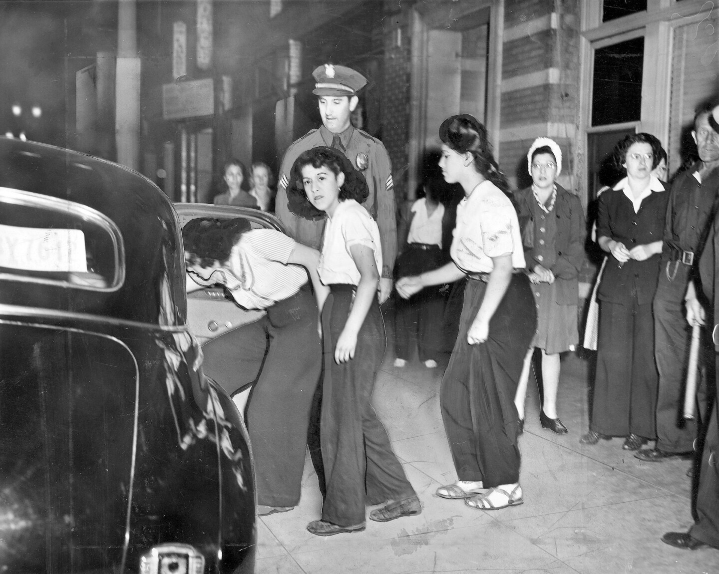 The 'black widow' girls gang, shown as they prepared to get into police car, 1942.