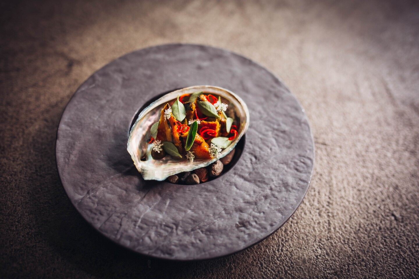 Three cup abalone, sits in a seashell placed atop a round, smooth gray slate. The dish is topped with green leaves and sliced chili.