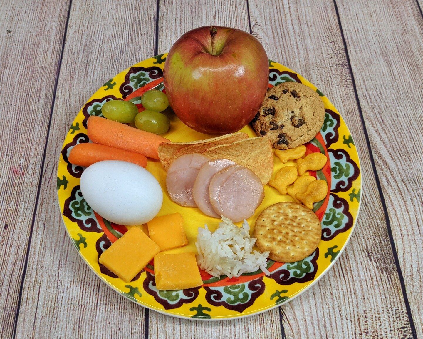 Snack items like  small crackers, apple slices and cheese squares are arranged on a plate