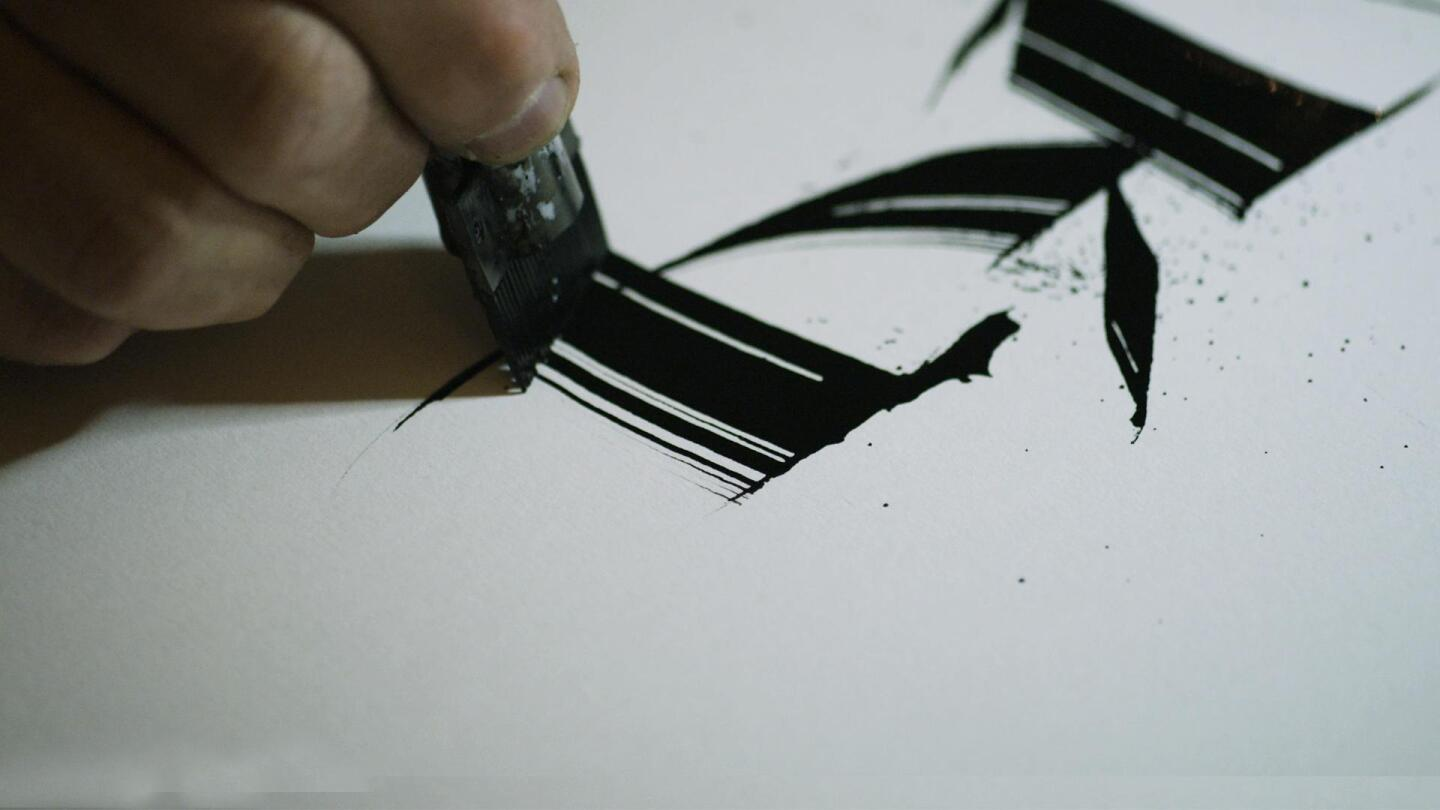 "A person doing calligraphy on a piece of paper. | From ""NOVA: A to Z - The First Alphabet"""