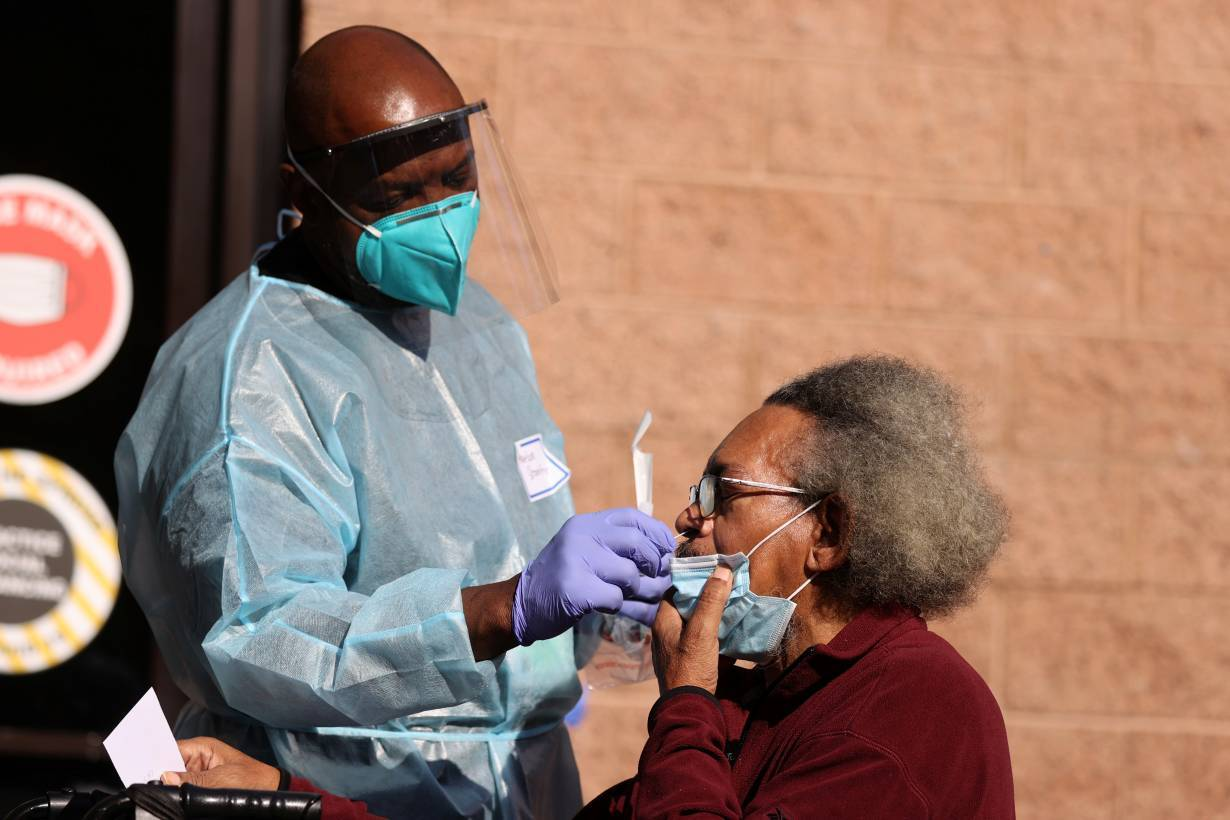 A nurse gives a person a coronavirus test at a Los Angeles Mission homeless shelter Thanksgiving meal giveaway, as the global outbreak of the coronavirus disease (COVID-19) continues, in Los Angeles, California, U.S., November 25, 2020.
