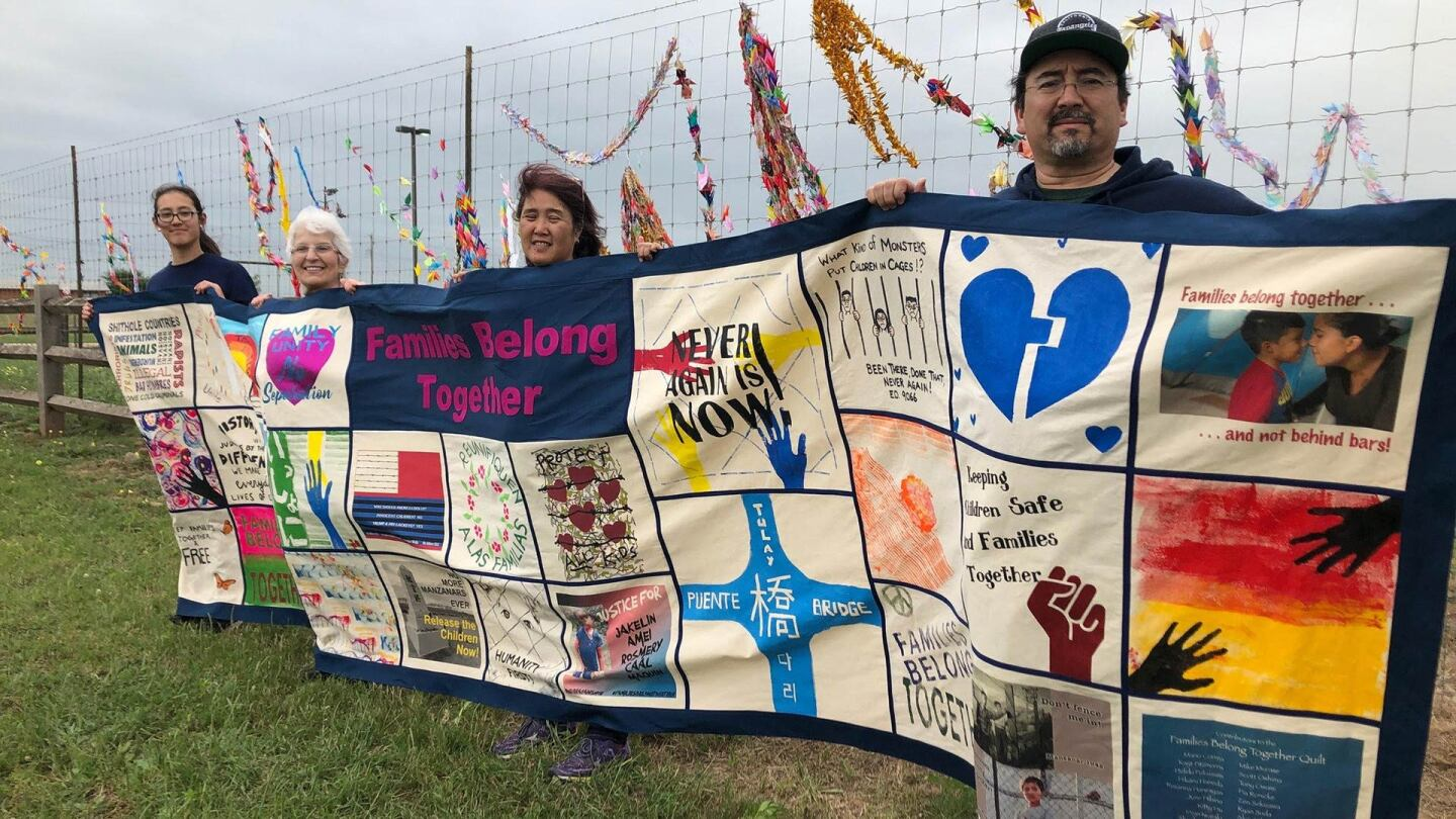 Four people hold a colorful quilt in protest