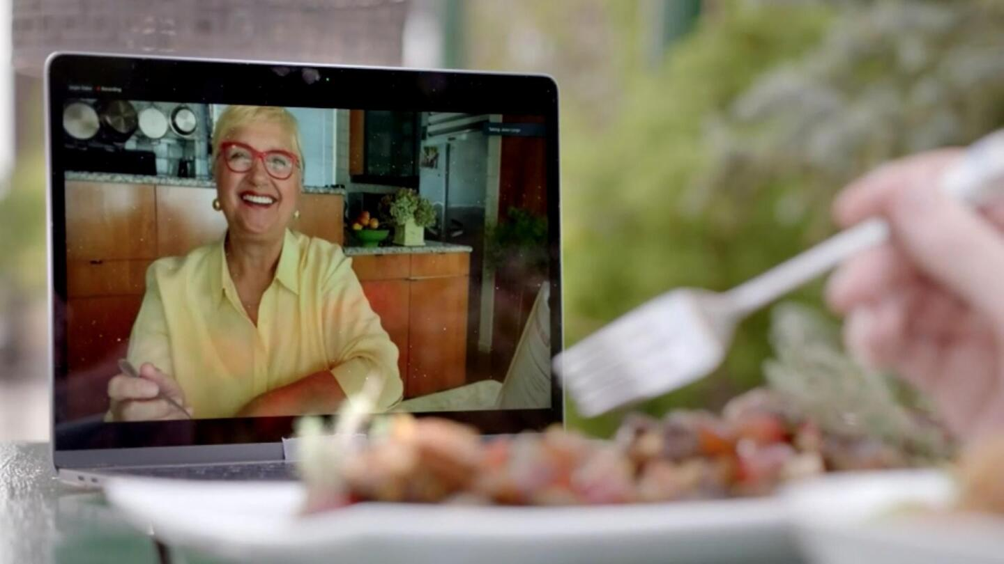 Chef Lidia Bastianich smiles on someone's laptop screen as they hover a fork over their plate of food.